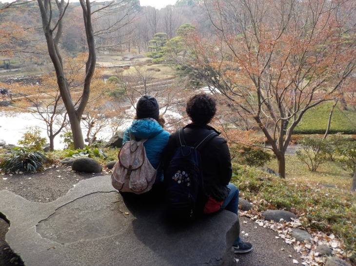 A sister and brother sit together on a rock, looking out over a winter garden.