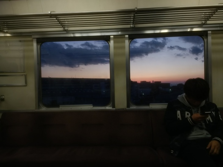 A mostly empty train, and the sunset viewed through two windows