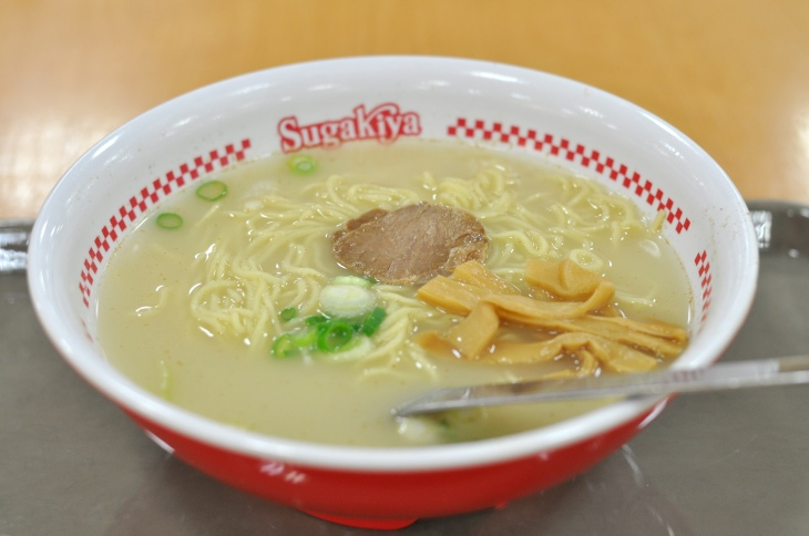 """A bowl of ramen in a bowl with the words """"Sugakiya"""""""