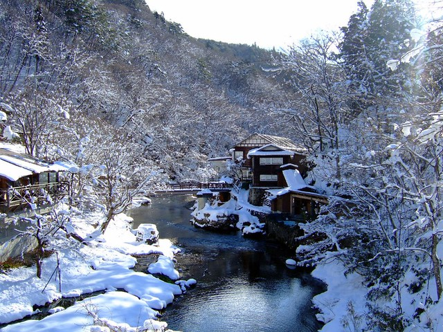 Ryokan covered in snow by river