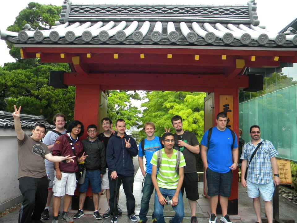 Group photo of study abroad student in front of Japanese temple gate