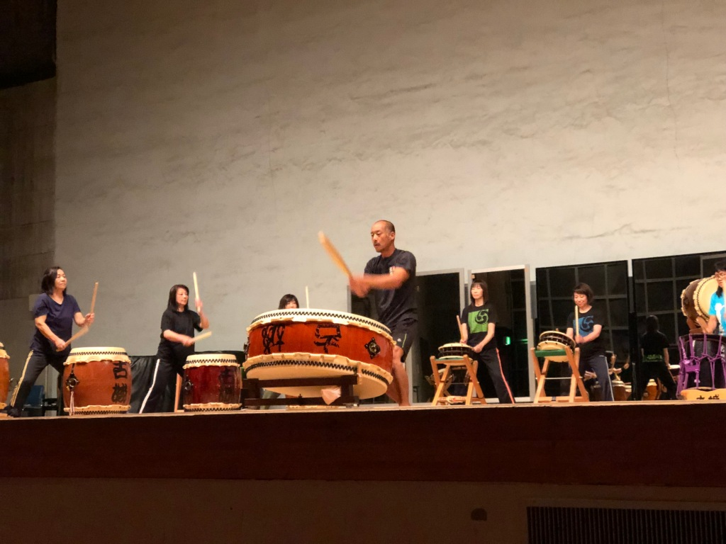 A man playing an Ohira-daiko drum in front of women playing Nagado and Shime-daiko drums